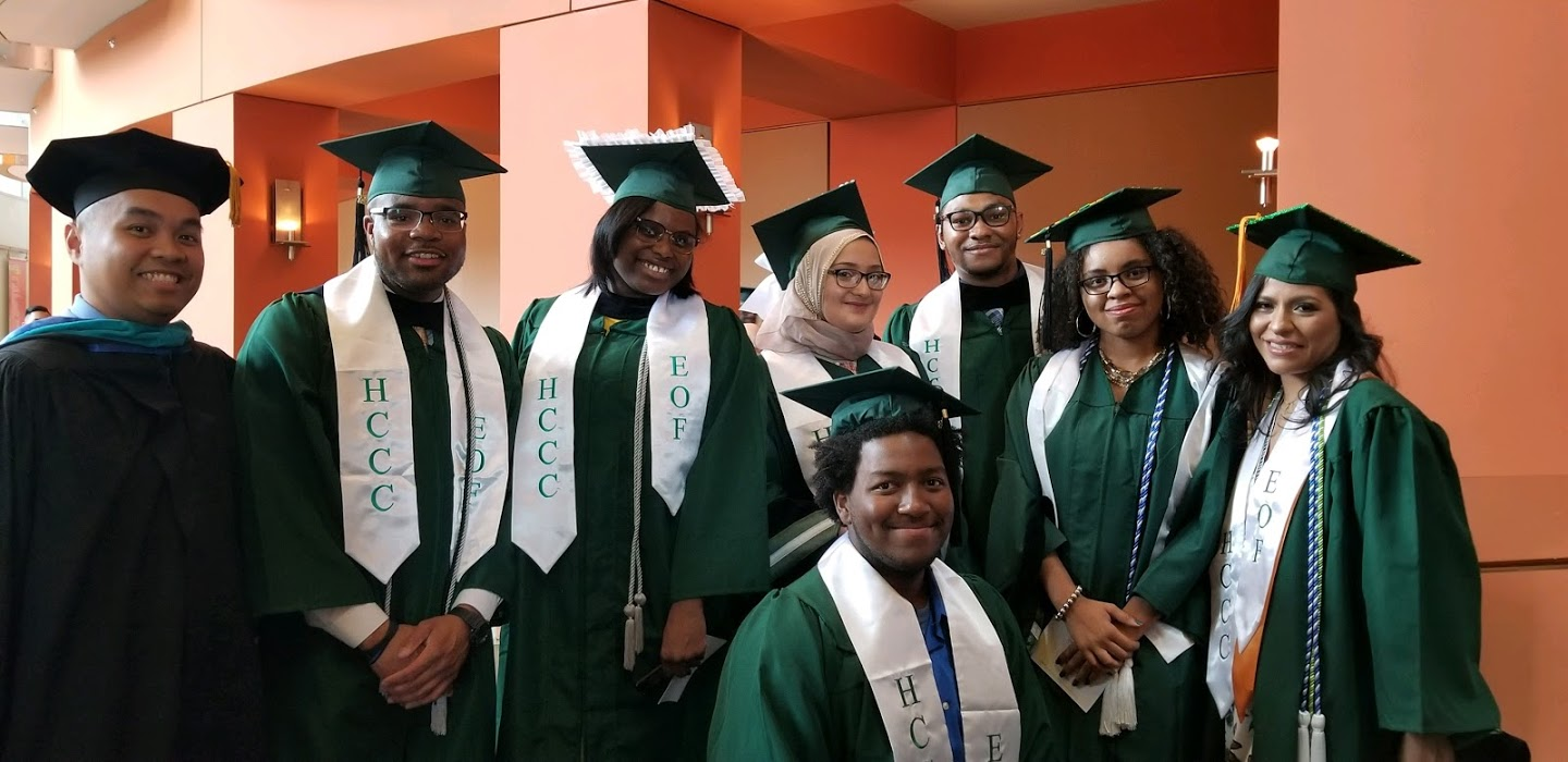 This is an image of 8 students in green cap and gowns at their graduation