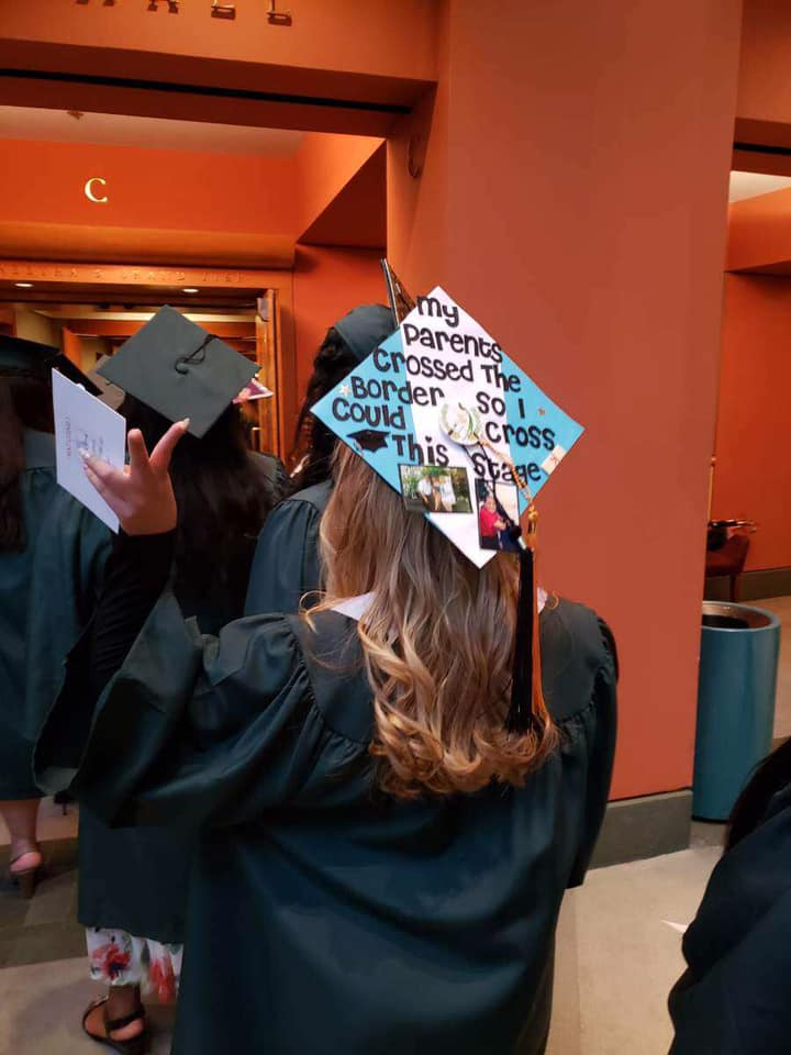 """The back of a student walking for graduation. On top of the cap it is personally styled by the student and it reads """" My parents crossed the border, so that I could cross this stage"""""""